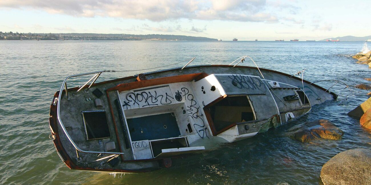 """According to the City of Vancouver, """"when an owner is not known or does not come forward, the City must pay the recovery and disposal costs."""" This boat has been sitting on the rocks at Sunset Beach in Vancouver since November 19. Photo by Tyrone Stelzenmuller."""